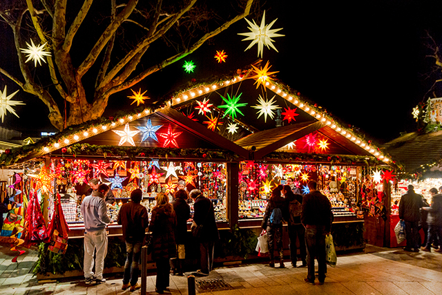 Stuttgart, Germany - December 21, 2013 - People shop at a stall selling decorative stars at the Christmas market at night on December 21, 2013 in Stuttgart.