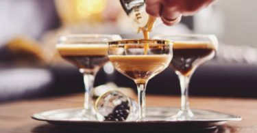 Male hands pouring espresso martini cocktail into glass