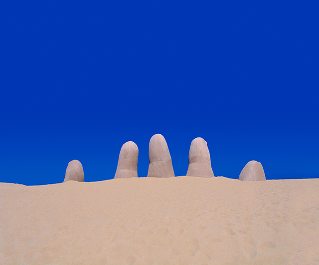 Beach finger sculpture rising from the sand with a cloudless blue sky in the background. Located in Punta del Este in Uruguay.
